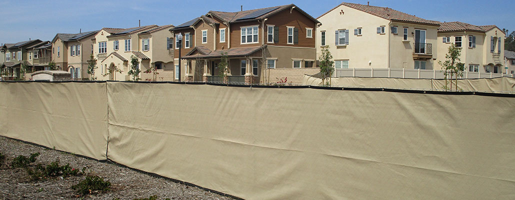 Temporary fence rental near Bowles, Fresno, California with beige privacy screen in front of homes.