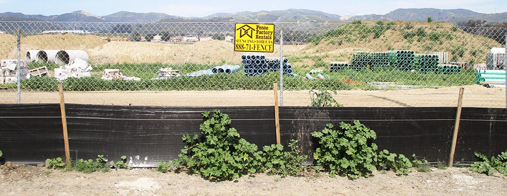 Carrizo Rd temporary fencing with debris netting at a construction site.